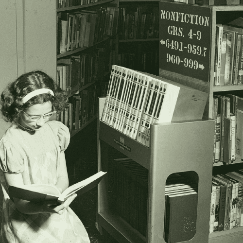 black and white photograph of young girl in a library